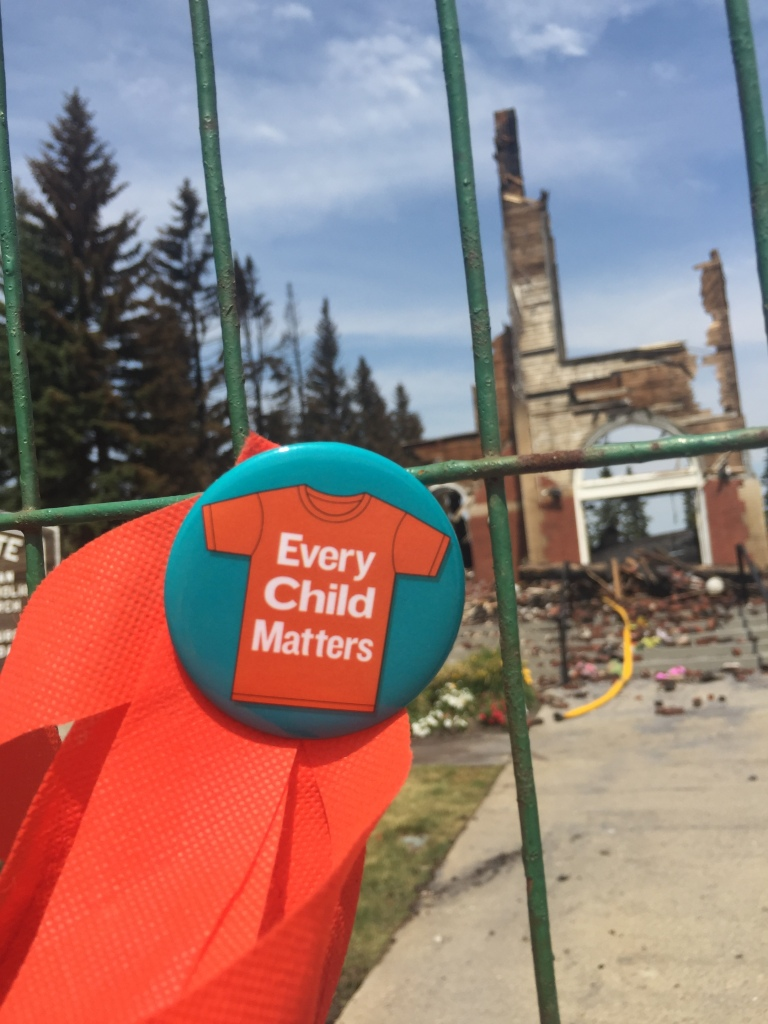 Every child matters pin with burnt church in back ground